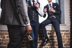 Hombre de negocios que sostiene el billete de banco del dólar y que mira a los colegas que beben el whisky, reunión del equipo de Foto de archivo libre de regalías