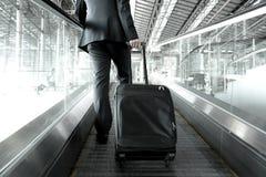 Hombre de negocios que sostiene el bolso de la carretilla que sube en la escalera móvil del aeropuerto Foto de archivo