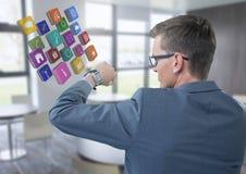 Hombre de negocios que sostiene el brazo con los iconos del reloj y de los apps a los ojos en oficina Imagen de archivo