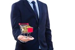 Hombre de negocios que sostiene el carro de la compra con la moneda de oro Fotos de archivo libres de regalías