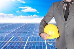 Hombre de negocios que sostiene el casco para trabajar en el poder de energía solar pl Foto de archivo libre de regalías