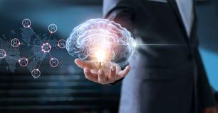 Hombre de negocios que sostiene el cerebro y la bombilla con establecimiento de una red global imagen de archivo