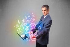 Hombre de negocios que sostiene el cuaderno con multimedias dibujadas mano colorida Foto de archivo