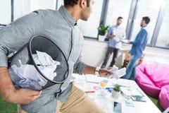Hombre de negocios que sostiene el cubo de la basura con los papeles y que mira a compañeros de trabajo fotos de archivo libres de regalías