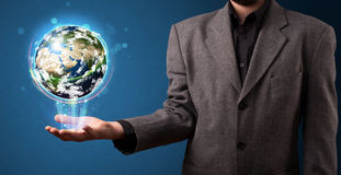 Hombre de negocios que sostiene el globo de la tierra que brilla intensamente Fotografía de archivo libre de regalías
