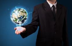 Hombre de negocios que sostiene el globo de la tierra que brilla intensamente Foto de archivo libre de regalías