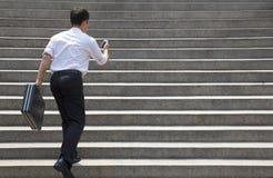 Hombre de negocios que sostiene el móvil y en prisa para correr para arriba en las escaleras fotos de archivo libres de regalías