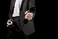 Hombre de negocios que sostiene el microteléfono de teléfono Foto de archivo libre de regalías