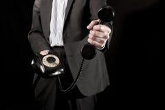 Hombre de negocios que sostiene el microteléfono de teléfono Foto de archivo