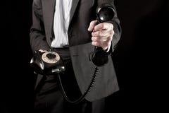Hombre de negocios que sostiene el microteléfono de teléfono Fotos de archivo