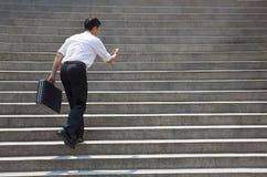 Hombre de negocios que sostiene el móvil y en prisa para correr para arriba en las escaleras Fotografía de archivo libre de regalías