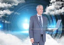 Hombre de negocios que sostiene el ordenador portátil con códigos binarios y las nubes en fondo imagen de archivo