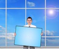 Hombre de negocios que sostiene el panel de plasma en blanco Imagen de archivo libre de regalías