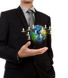Hombre de negocios que sostiene el pequeño mundo de la red social Imagen de archivo libre de regalías