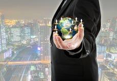 Hombre de negocios que sostiene el pequeño mundo en sus manos con paisaje urbano Imagenes de archivo