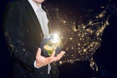 Hombre de negocios que sostiene el pequeño mundo en sus manos contra americ Imagen de archivo