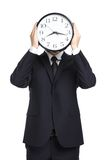 Hombre de negocios que sostiene el reloj delante de su cara imagenes de archivo