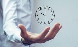 Hombre de negocios que sostiene el reloj Gestión de tiempo del negocio imagenes de archivo