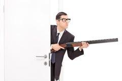 Hombre de negocios que sostiene el rifle y que entra en un cuarto Foto de archivo