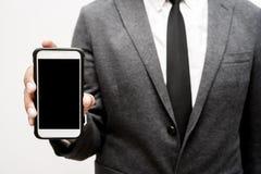 Hombre de negocios que sostiene el teléfono elegante Fotografía de archivo