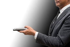 Hombre de negocios que sostiene el teléfono elegante Imagen de archivo