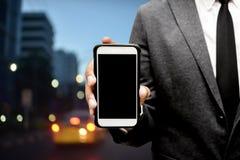 Hombre de negocios que sostiene el teléfono elegante con el fondo de la luz de la ciudad Foto de archivo libre de regalías