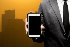Hombre de negocios que sostiene el teléfono elegante con el fondo de la luz de la ciudad Imagenes de archivo