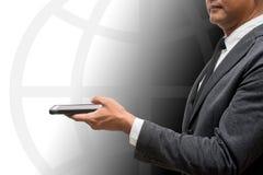 Hombre de negocios que sostiene el teléfono elegante con el gráfico del globo en backgroun Imagenes de archivo