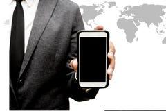 Hombre de negocios que sostiene el teléfono elegante con el gráfico del mapa del mundo Foto de archivo