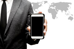 Hombre de negocios que sostiene el teléfono elegante con el gráfico del mapa del mundo Fotografía de archivo libre de regalías