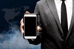 Hombre de negocios que sostiene el teléfono elegante con humo en fondo Imagen de archivo libre de regalías