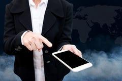 Hombre de negocios que sostiene el teléfono elegante con humo en fondo Foto de archivo libre de regalías