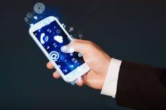 Hombre de negocios que sostiene el teléfono elegante con los medios iconos Foto de archivo libre de regalías