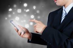 Hombre de negocios que sostiene el teléfono elegante que muestra el icono, estrategia empresarial Foto de archivo