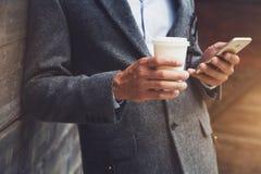 Hombre de negocios que sostiene el teléfono de la lectura del café Foto de archivo libre de regalías