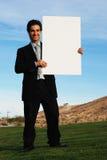 Hombre de negocios que sostiene el verraco en blanco imagenes de archivo