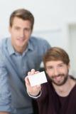 Hombre de negocios que sostiene hacia fuera una tarjeta de visita en blanco Foto de archivo libre de regalías