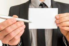 Hombre de negocios que sostiene hacia fuera una tarjeta en blanco y una pluma Imágenes de archivo libres de regalías