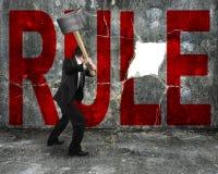 Hombre de negocios que sostiene la almádena que golpea palabra roja de la regla en concre Fotografía de archivo
