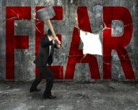 Hombre de negocios que sostiene la almádena que golpea palabra roja del MIEDO en concre Imagenes de archivo