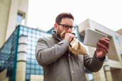 Hombre de negocios que sostiene la bolsa de papel sobre boca como si teniendo un ataque de pánico imagenes de archivo