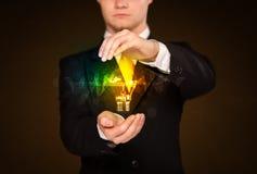 Hombre de negocios que sostiene la bombilla Imagen de archivo libre de regalías