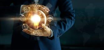 Hombre de negocios que sostiene la bombilla que brilla intensamente con el icono de las fuentes de energía fotografía de archivo