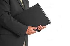 Hombre de negocios que sostiene la carpeta cerrada Foto de archivo libre de regalías