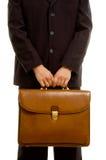 Hombre de negocios que sostiene la cartera marrón Foto de archivo