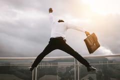 Hombre de negocios que sostiene la cartera que salta para la alegría que celebra un succ fotografía de archivo