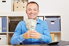 Hombre de negocios que sostiene la fan del dinero del dólar Imagen de archivo libre de regalías