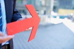 Hombre de negocios que sostiene la flecha roja Foto de archivo libre de regalías