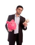 Hombre de negocios que sostiene la hucha con el dinero Imagen de archivo libre de regalías