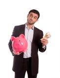 Hombre de negocios que sostiene la hucha rosada con el dinero disponible Imagen de archivo libre de regalías